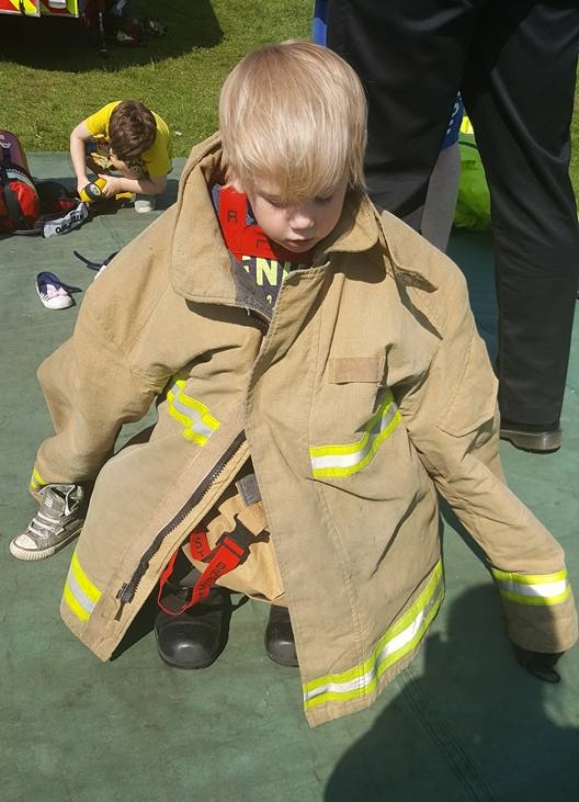 Trying on fireman outfit at Open Farm Sunday