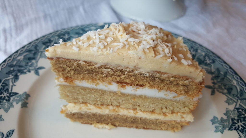 Coconut coffee cake slice with coffee buttercream icing and coconut icing and coconut flakes on top