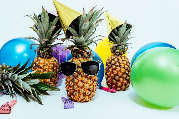 Pineapple wearing a party hat and sunglasses. Balloons. Children's party.