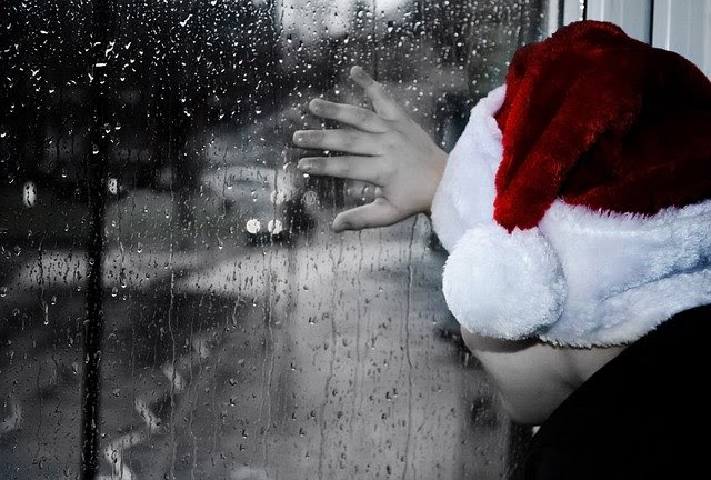 child stood with hand on rainy window with a Santa hat on, How To Survive This COVID Christmas
