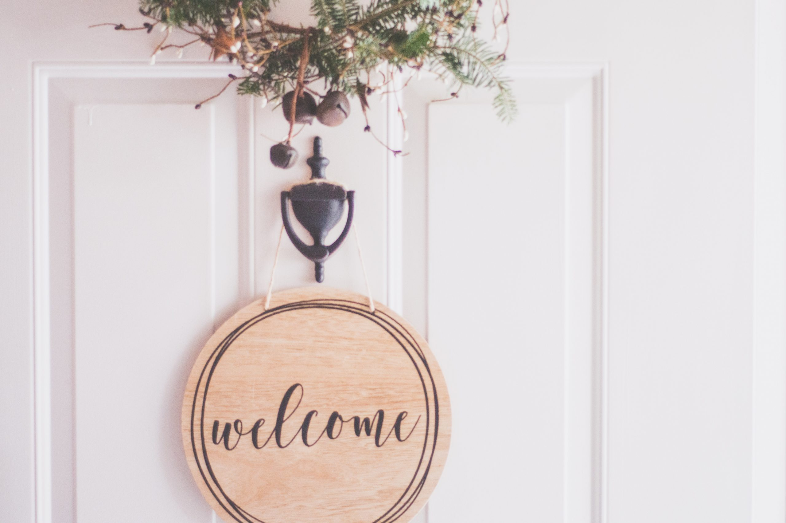 wooden welcome sign on a white door, 5 Ways To Up Your Home's Security