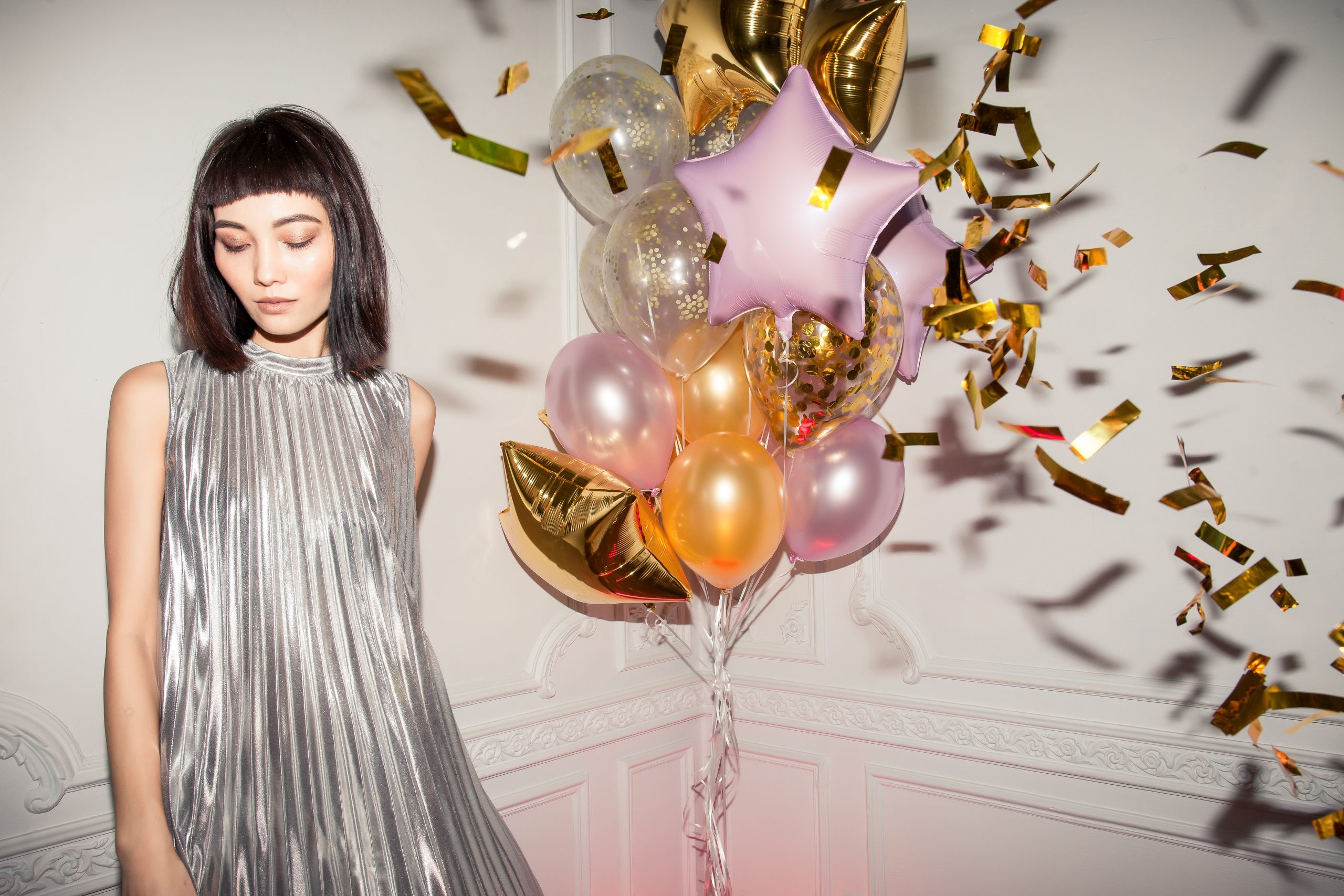 woman in grey party dress stood next to a bunch of balloons; Planning For The Post-Covid Party Of Your Dreams