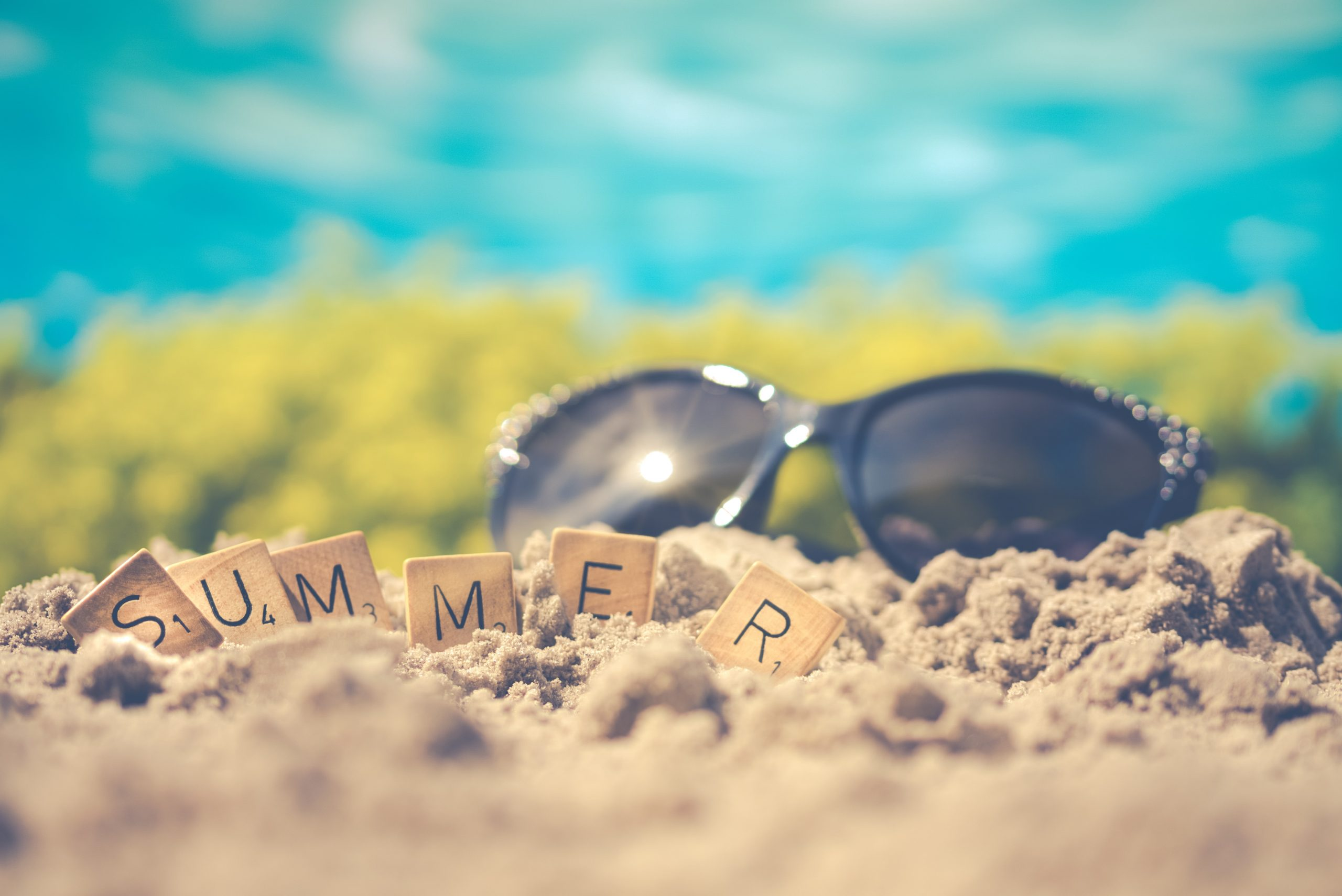 """""""Summer"""" written out in scrabble letters in front of black sunglasses on the sand; 3 Ways to Keep Your Home Cool in the Summer"""