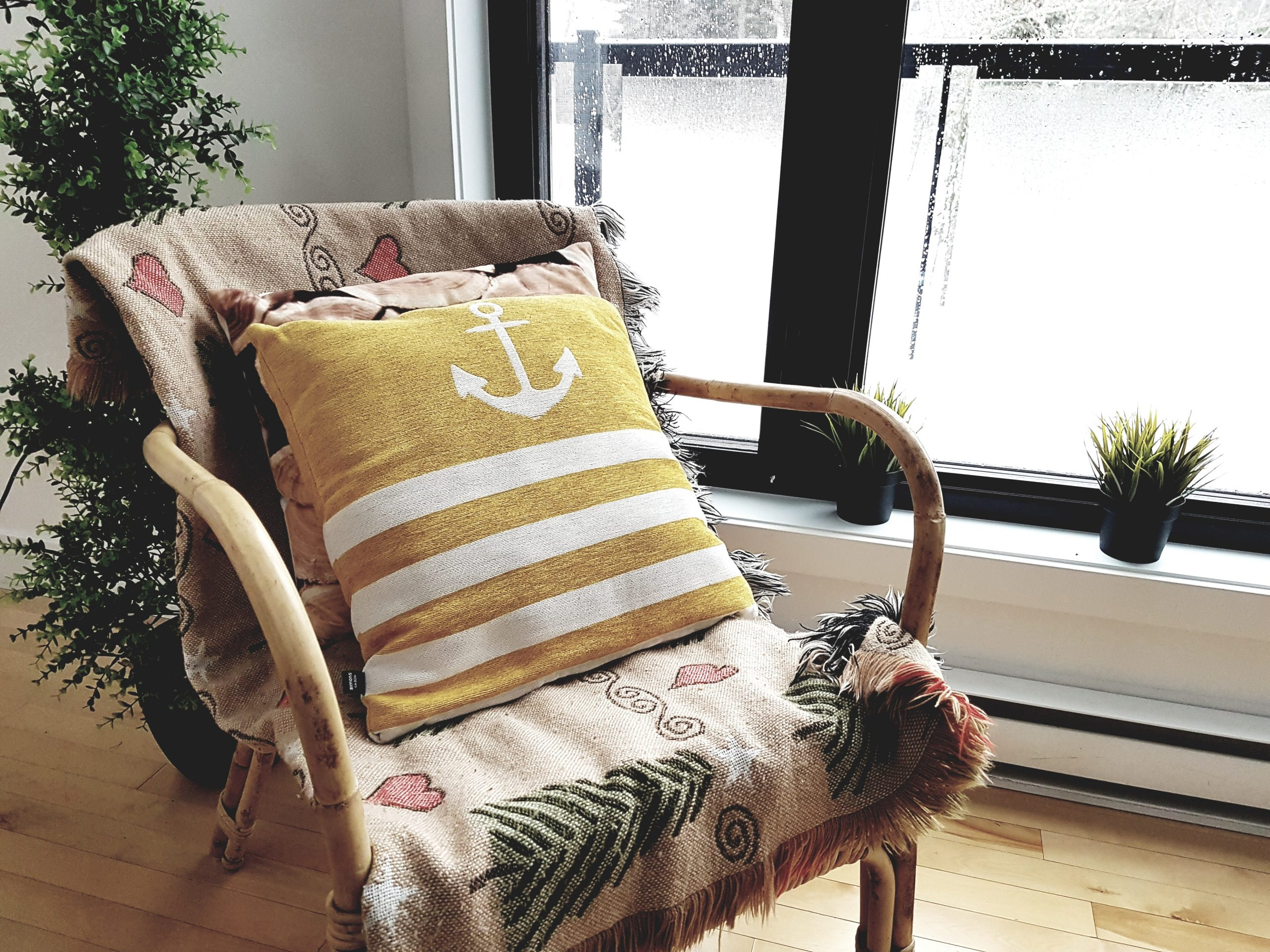 wicker chair covered by a patterned throw and yellow nautical cushion