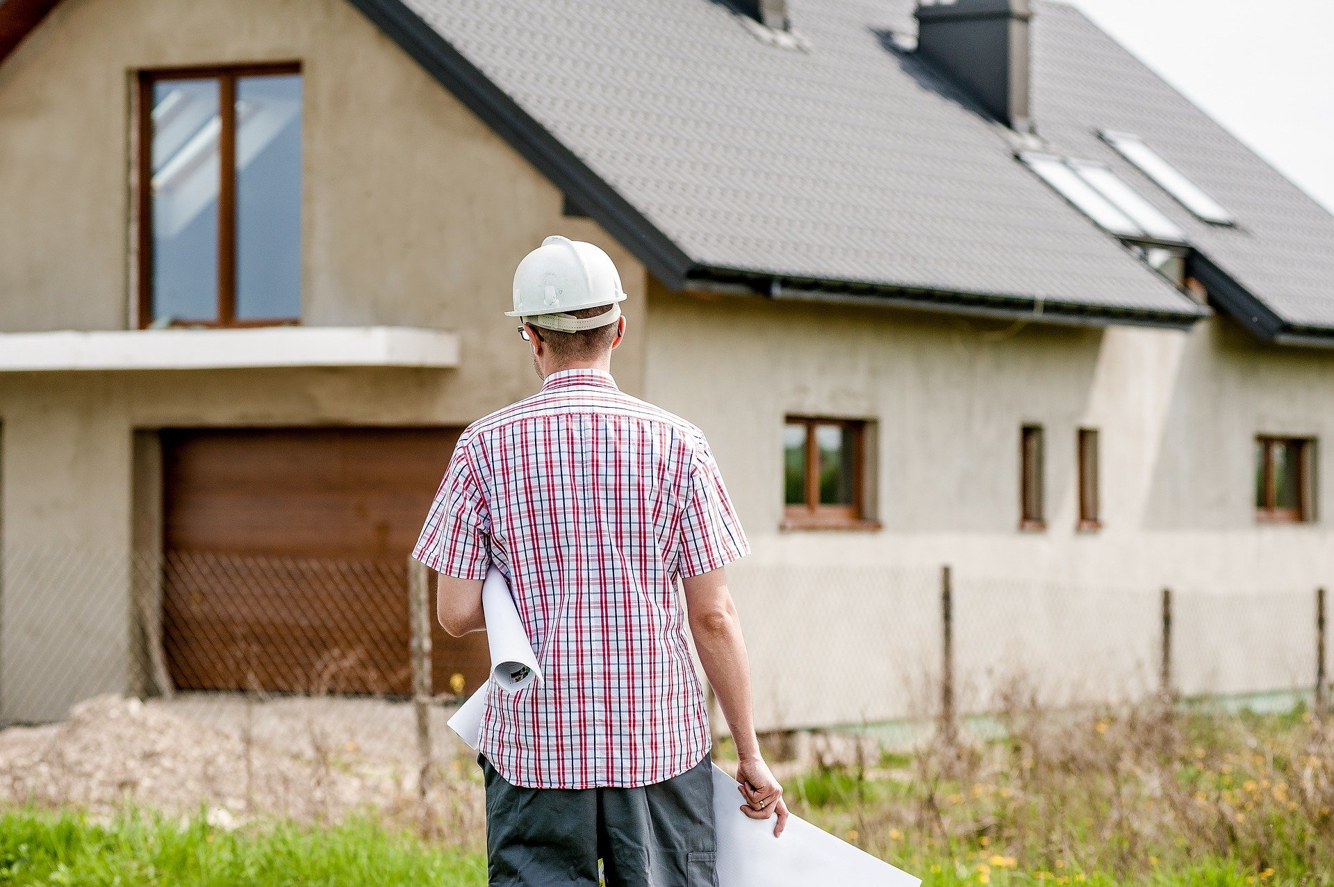 main in hard hat walking towards a house; How Not To Blow The Budget On Your House Building Project