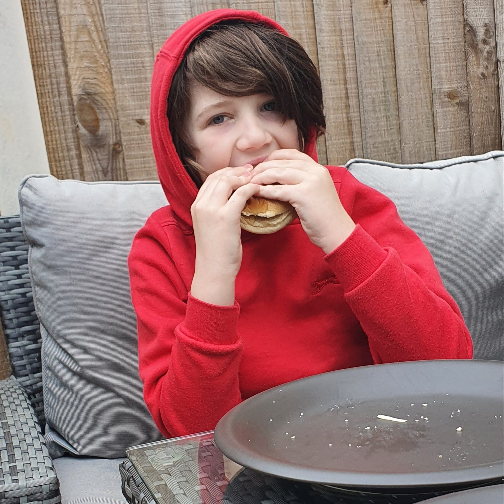 a child in a red hoody eating a cheeseburger