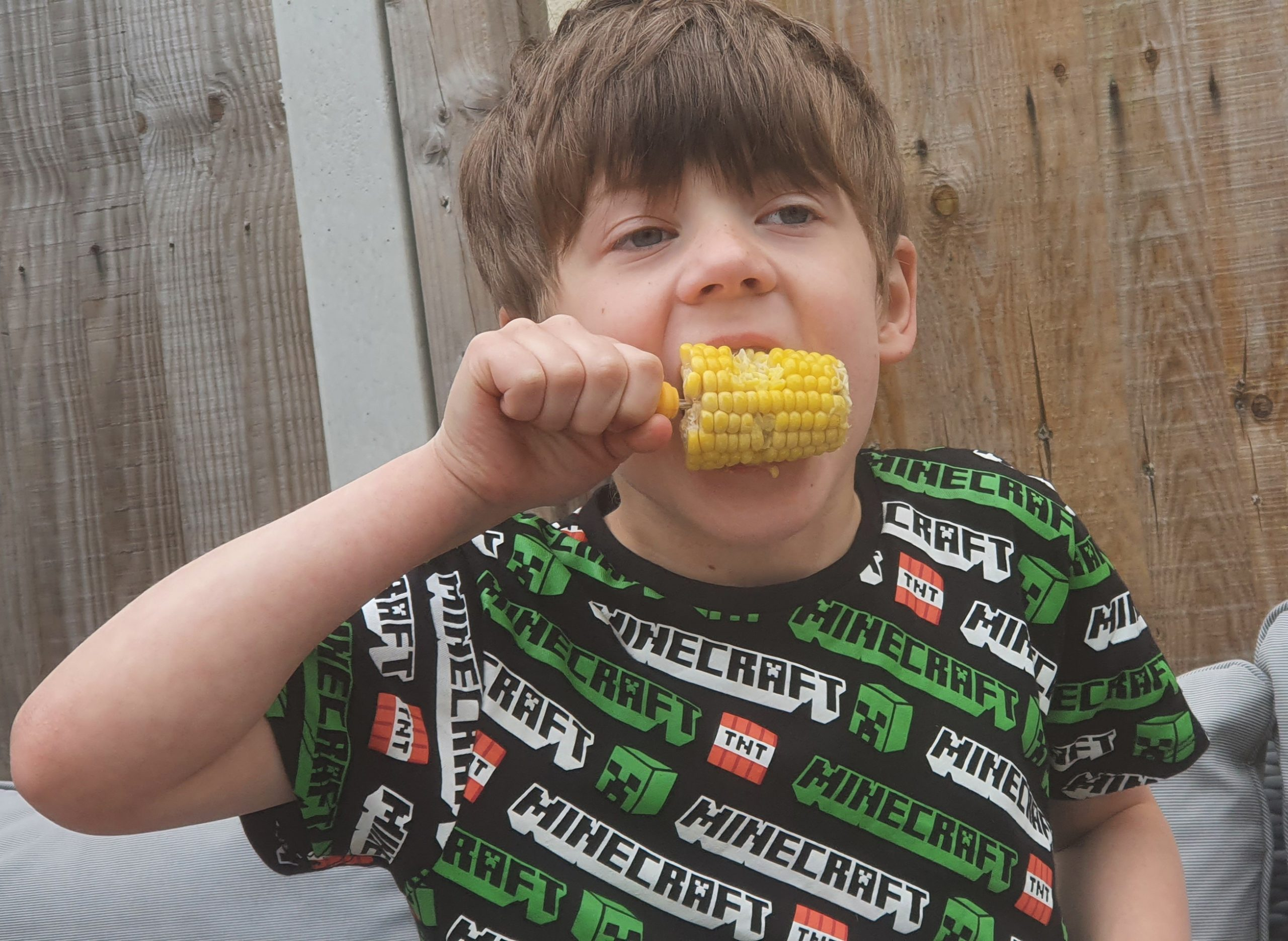a child in a Minecraft t-shirt eating a corn on the cob