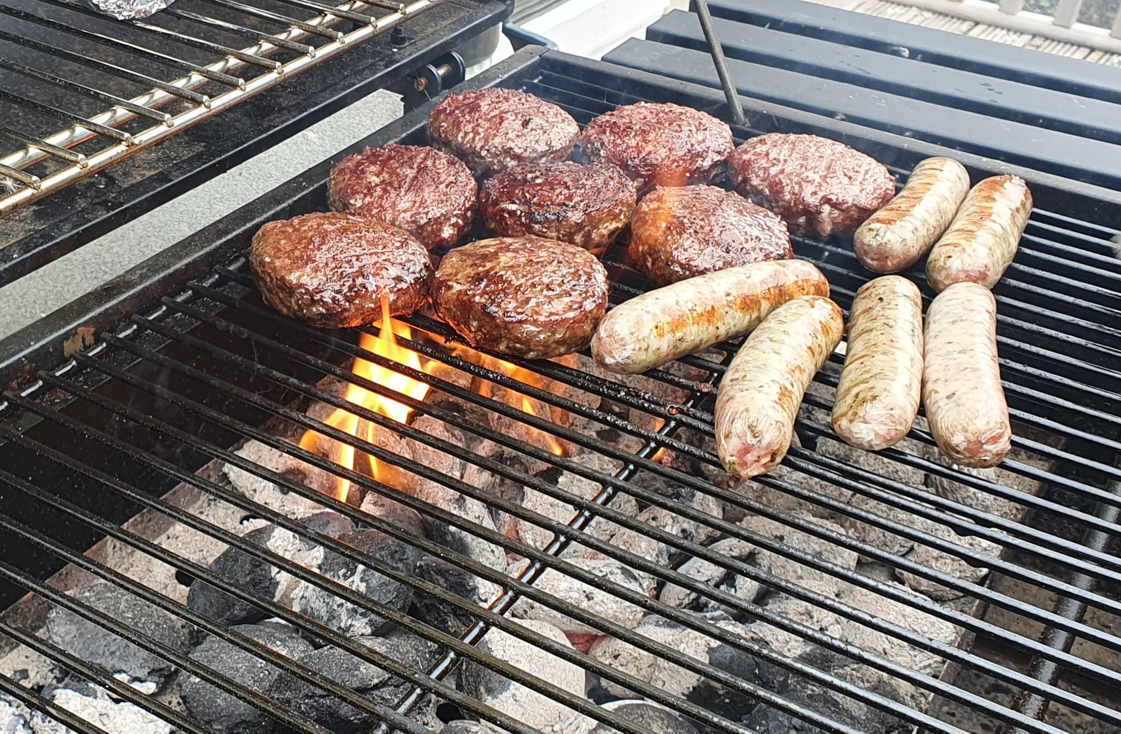 sausages and burgers grilling on a barbecue