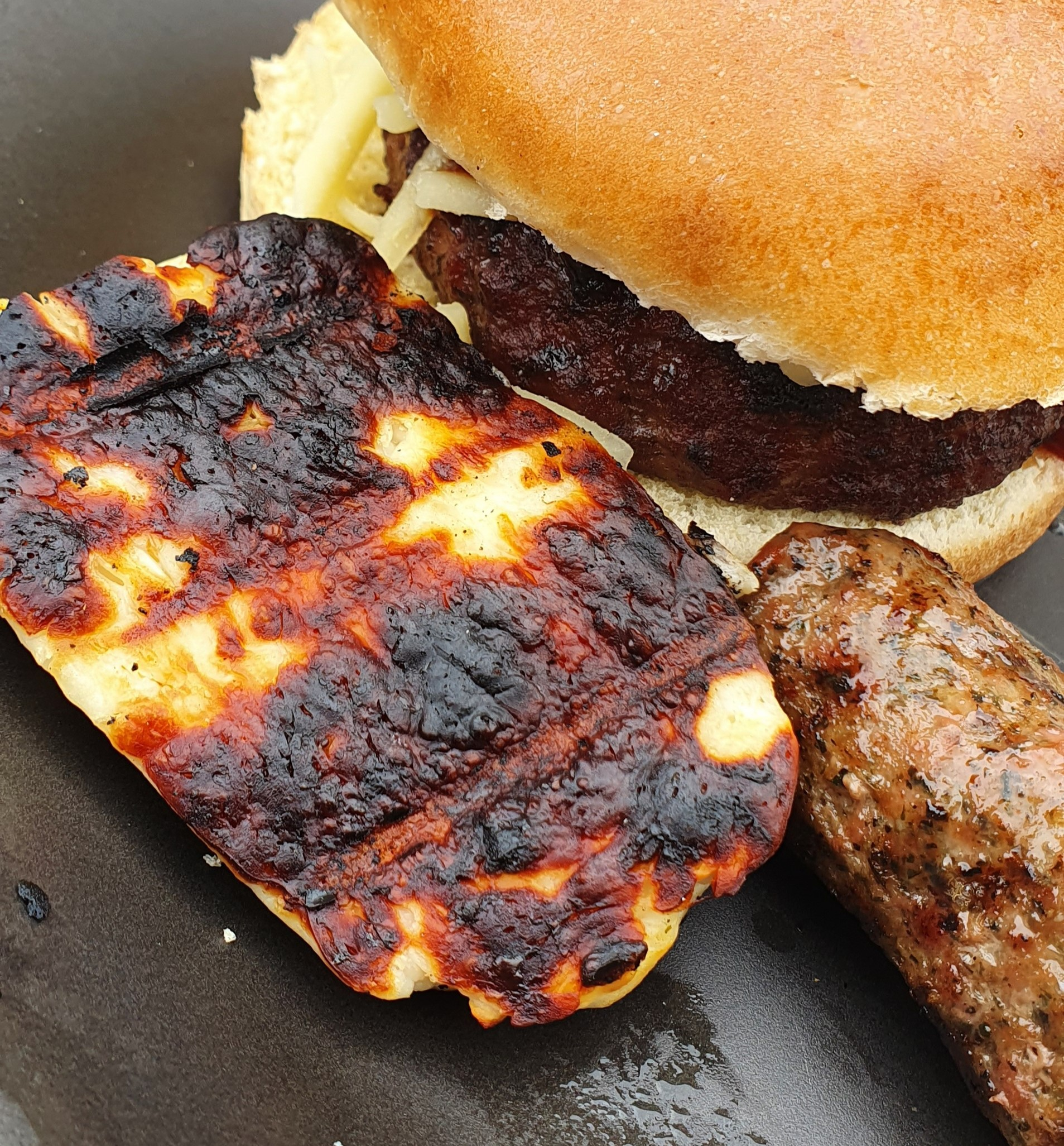 a piece of BBQ charred halloumi sat next to a burger