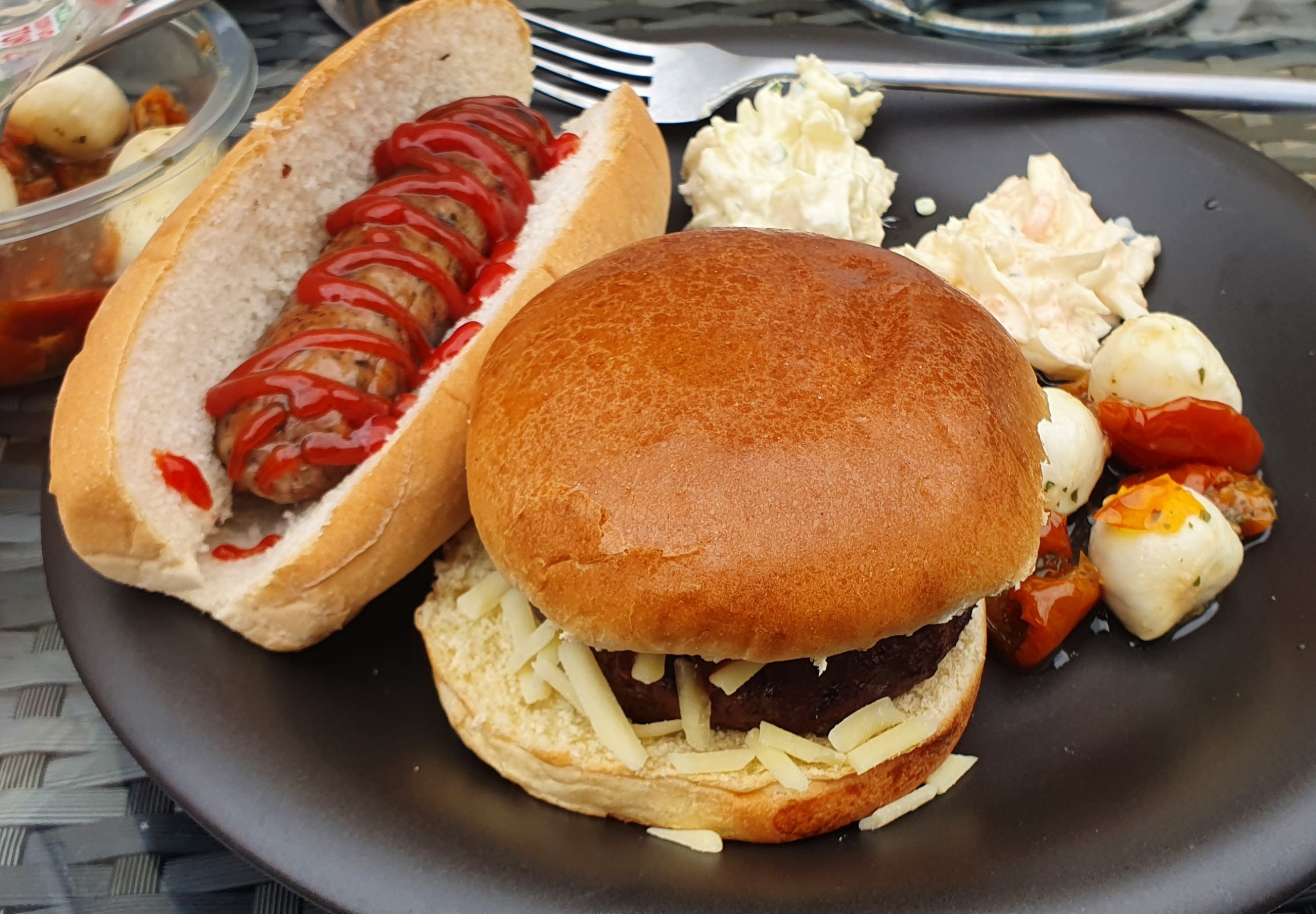 a cheeseburger and a hot dog on a black plate