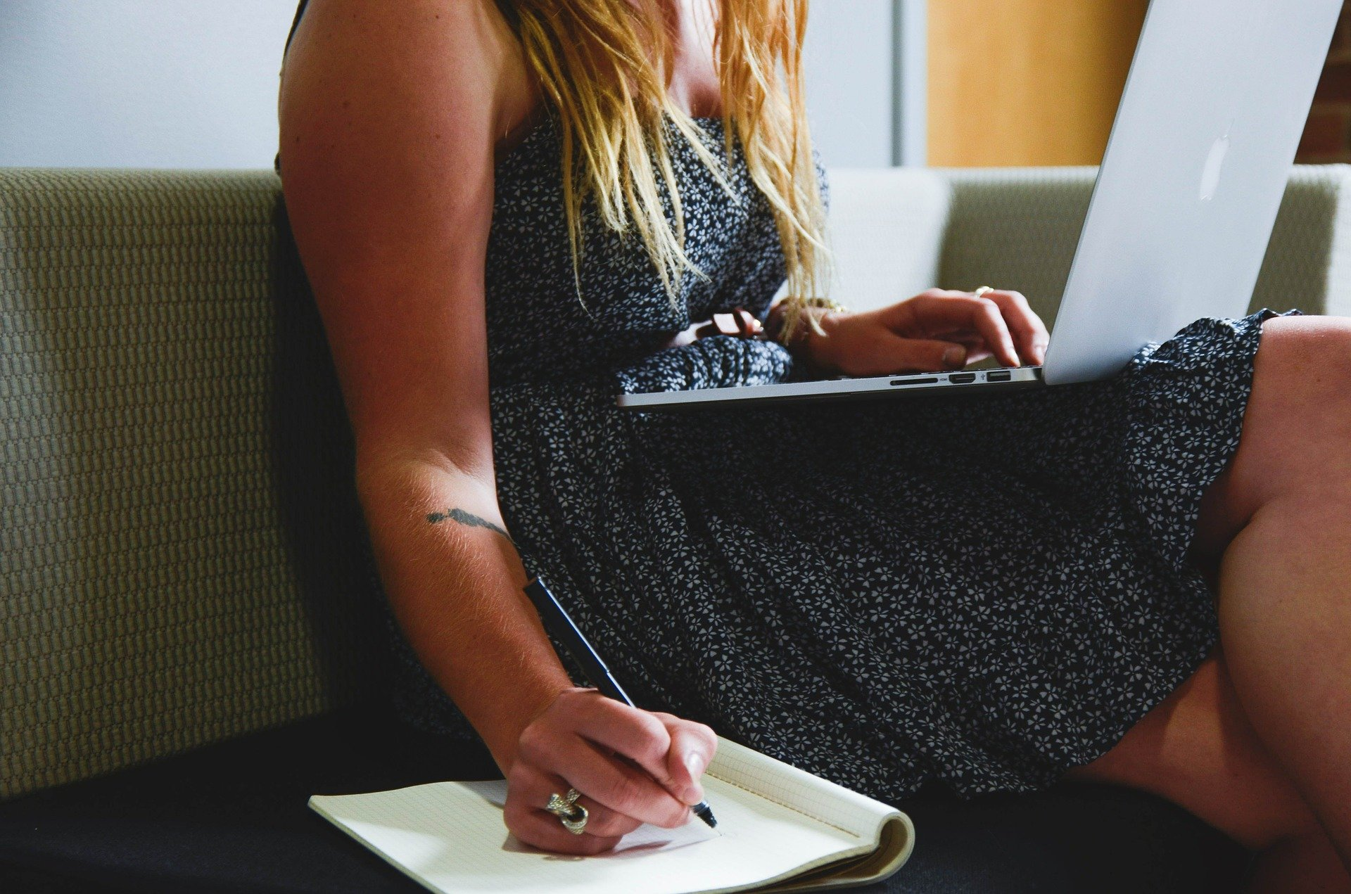 woman on writing on a notepad and typing on laptop; Tips on How to Boost Your Immunity When Working From Home