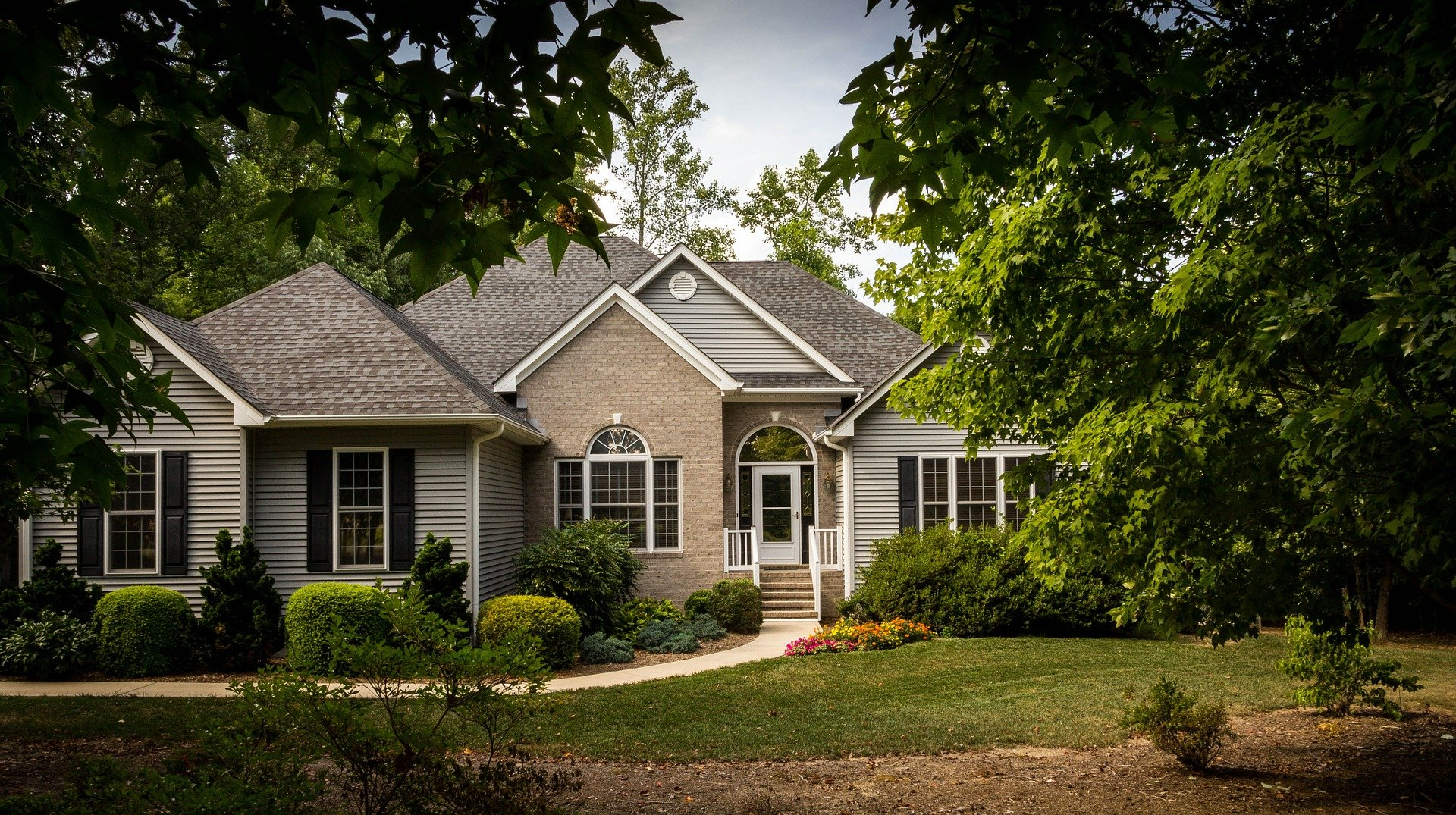 large grey house with green lawn in front; 4 Home Maintenance Tips To Keep Your Home In Shape