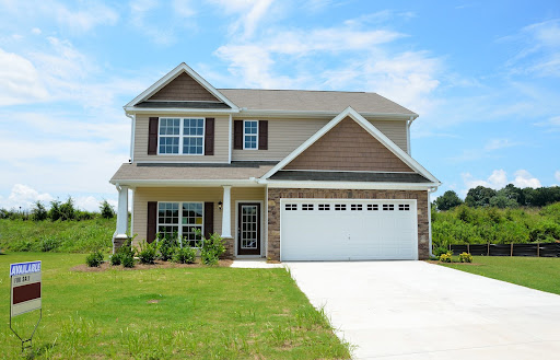 a large house at the end of a driveway; Moving Into Your First Home Get These Done