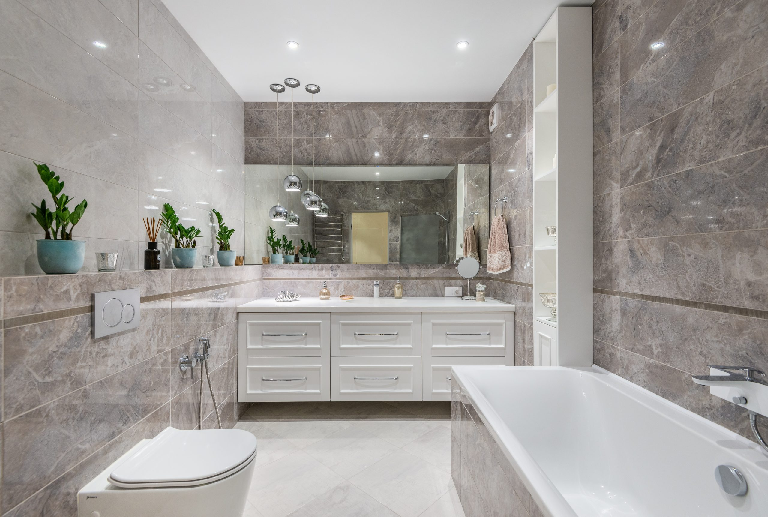 large white bathroom with a tub, toilet, and sinks; Thinking About Renovating Your Home Tackle These Projects First!